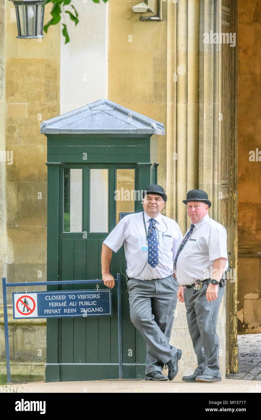 Un paio di burly maschio, Bowler cappello guardie di sicurezza stand sul dazio con l ingresso di nuovi (aka King's) Corte al Trinity College, Università di Cambri Immagini Stock