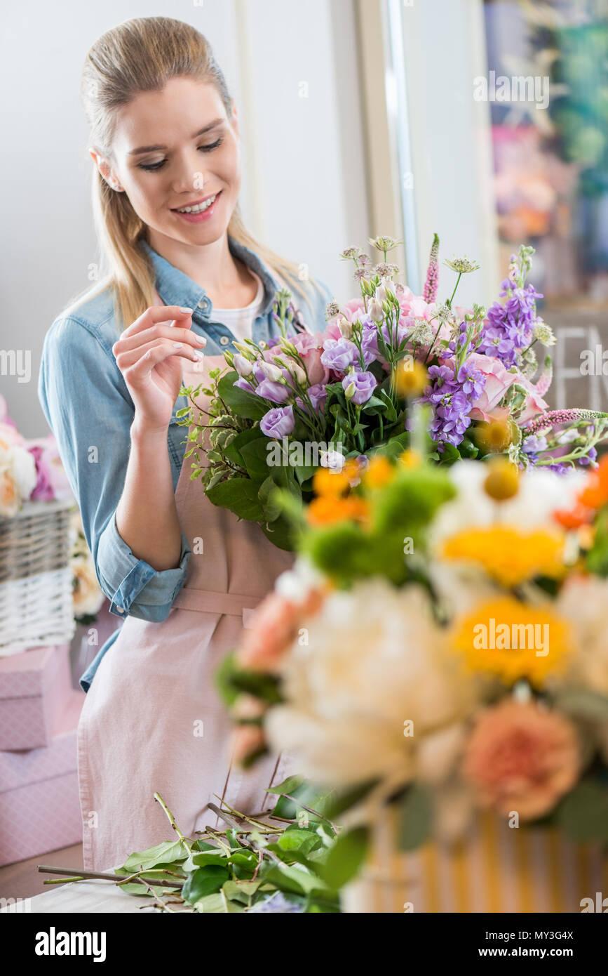 Attraente donna sorridente nel grembiule holding bouquet e disponendo dei fiori nel negozio di fiori Immagini Stock