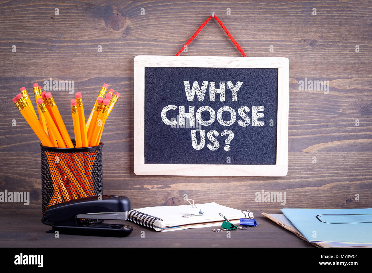 Perché scegliere noi. Chalkboard su uno sfondo di legno Immagini Stock
