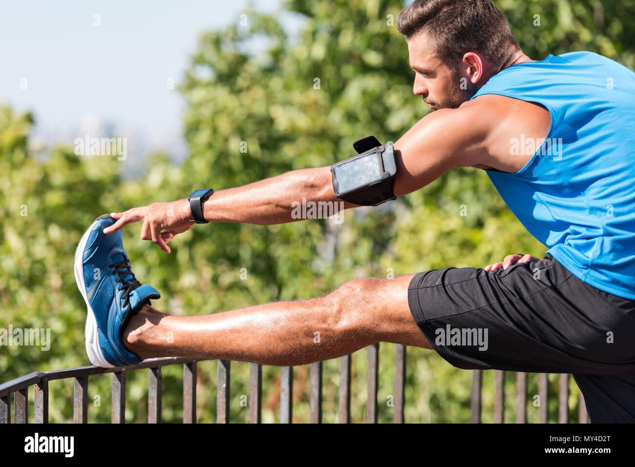 Sportivo con lo smartphone nella fascia braccio stretching in posizione di parcheggio Immagini Stock