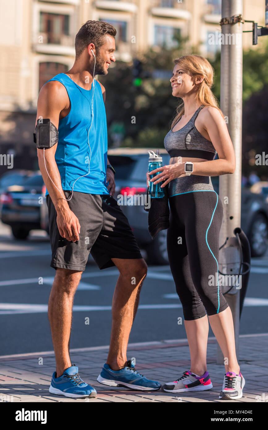 Athletic sportive con Borraccia sportiva e sportivo con lo smartphone nella fascia braccio in città Immagini Stock