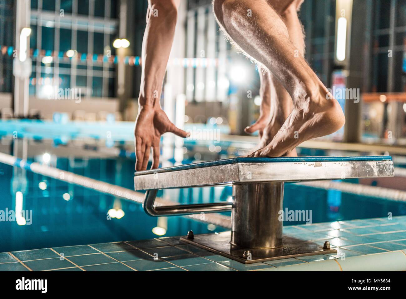 Vista ritagliata del nuotatore in piedi sul trampolino pronti a saltare in concorrenza piscina Immagini Stock
