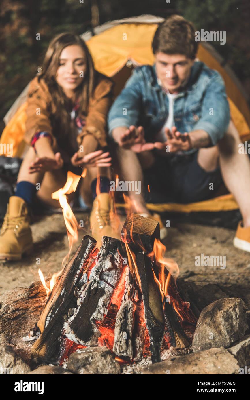 Giovane riscaldando le mani con il falò sul viaggio escursionistico Immagini Stock