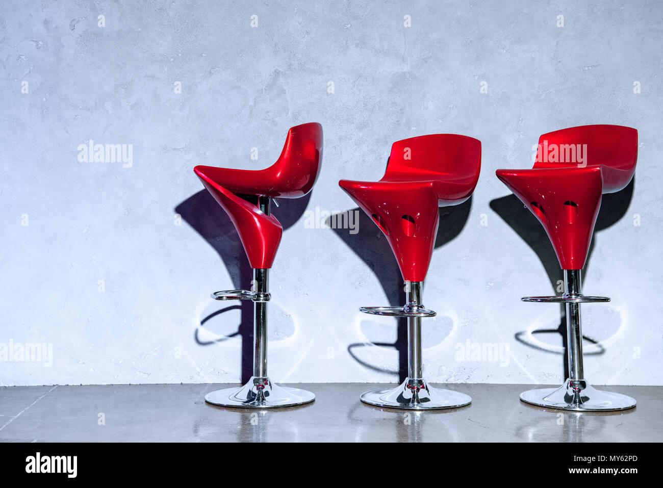 Tre rossi vuoto sgabelli bar vicino al muro grigio foto & immagine
