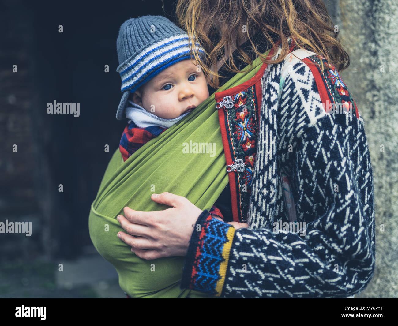 Una giovane madre con il suo bambino in un vettore imbracatura è in piedi al di fuori di un edificio storico Immagini Stock