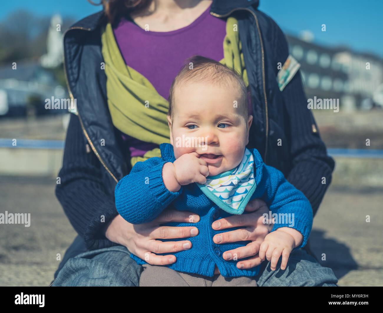 Una giovane madre è rilassante con il suo bambino al di fuori Immagini Stock