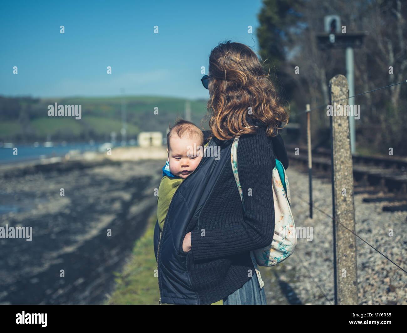 Una giovane madre sta portando il suo bambino in una imbracatura all'aperto Immagini Stock