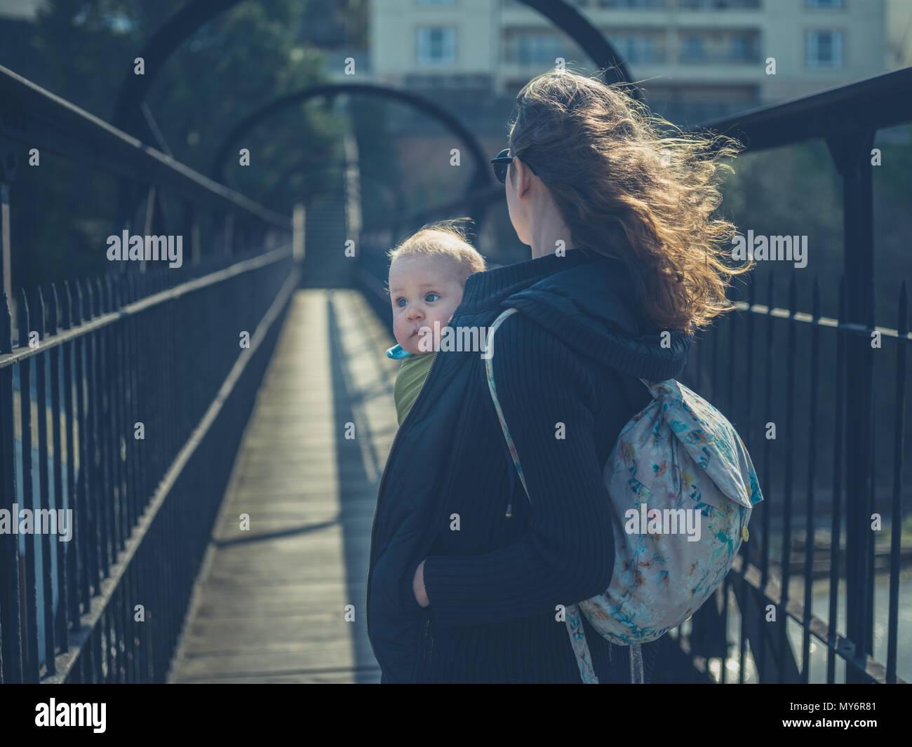 Una giovane madre è in piedi su una passerella con il suo bambino in una imbracatura Immagini Stock