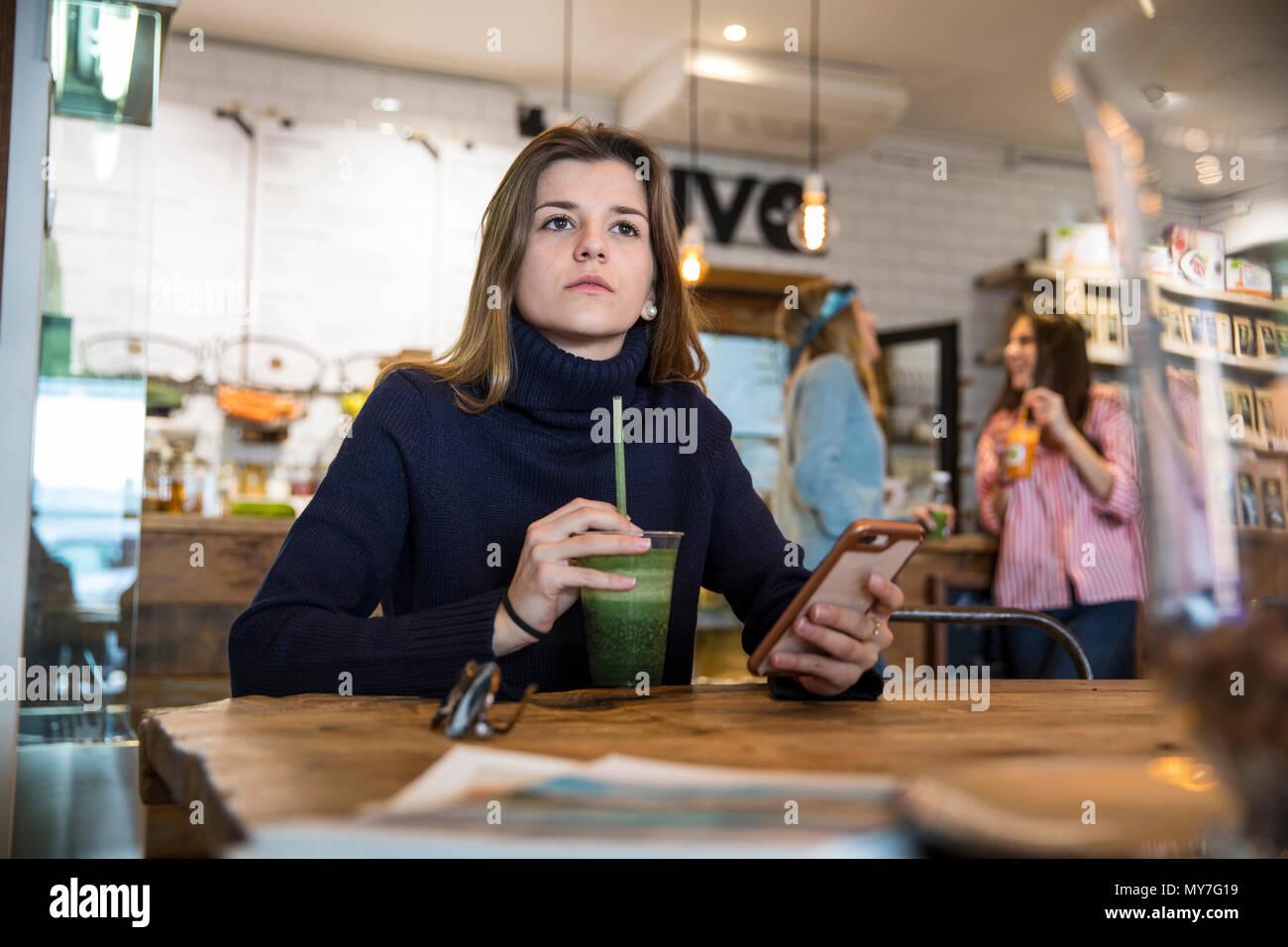 Giovane donna seduta al cafe, tenendo lo smartphone, frullato potabile Immagini Stock
