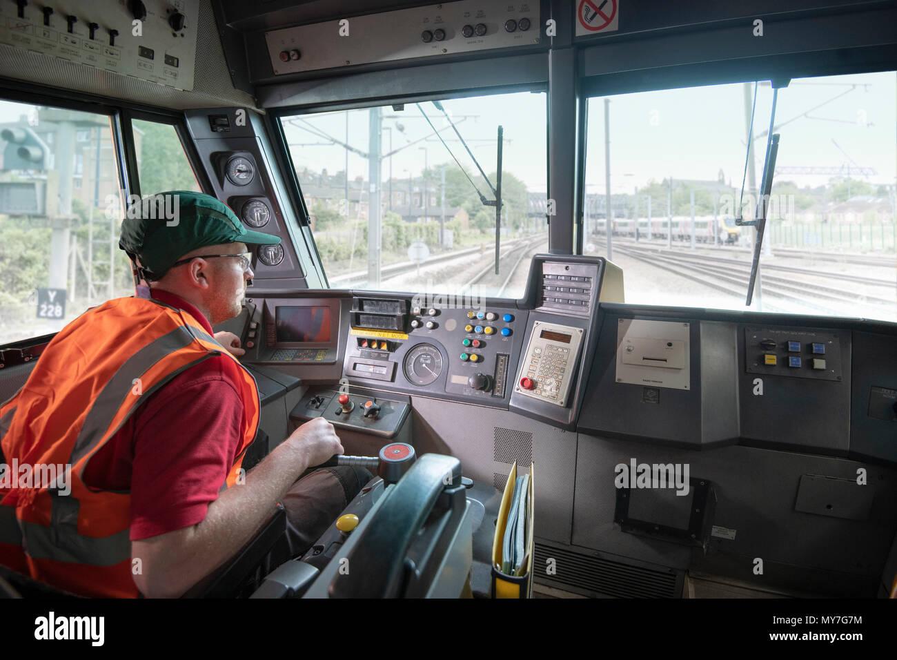 Macchinista nella locomotiva fisso sui binari del treno Immagini Stock
