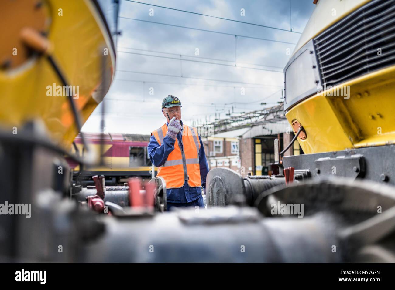 Ingegnere utilizzando un walkie-talkie di locomotiva di guida Immagini Stock
