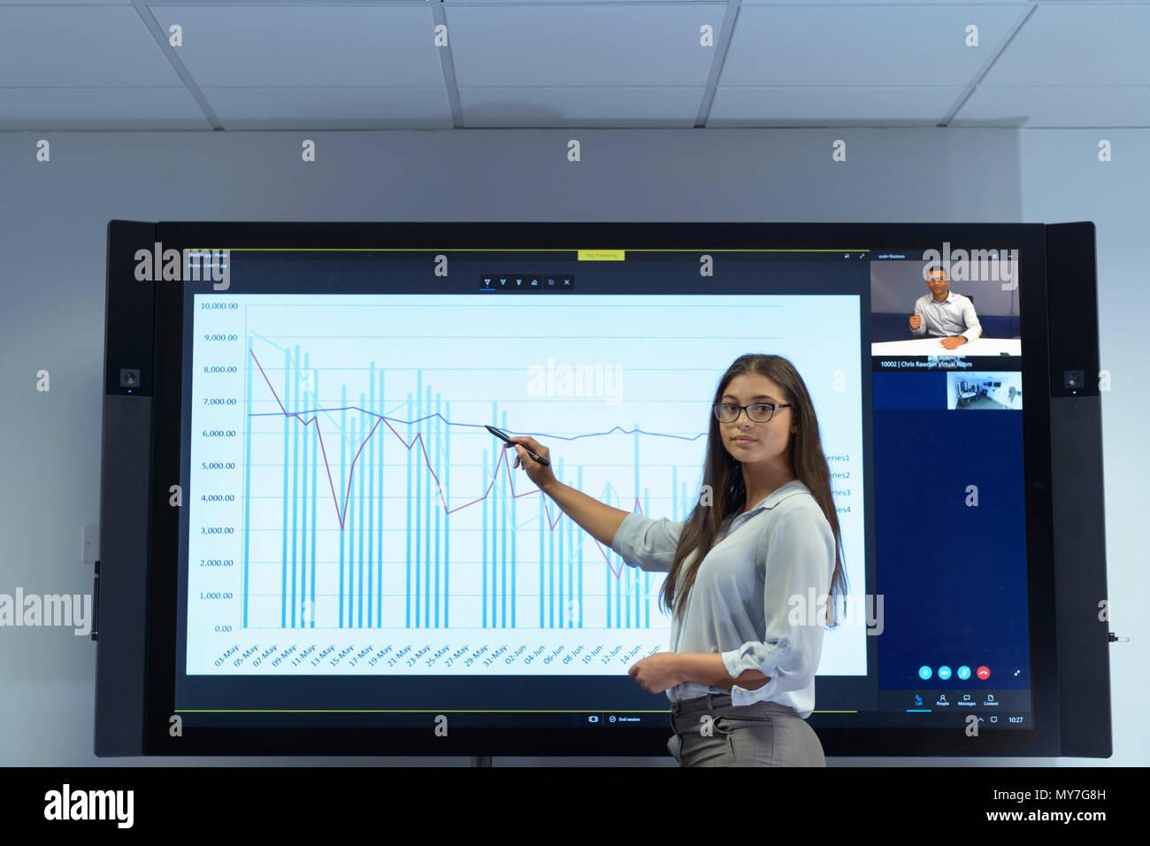 Donna presentando business meeting con il grafico e video conferenze Immagini Stock