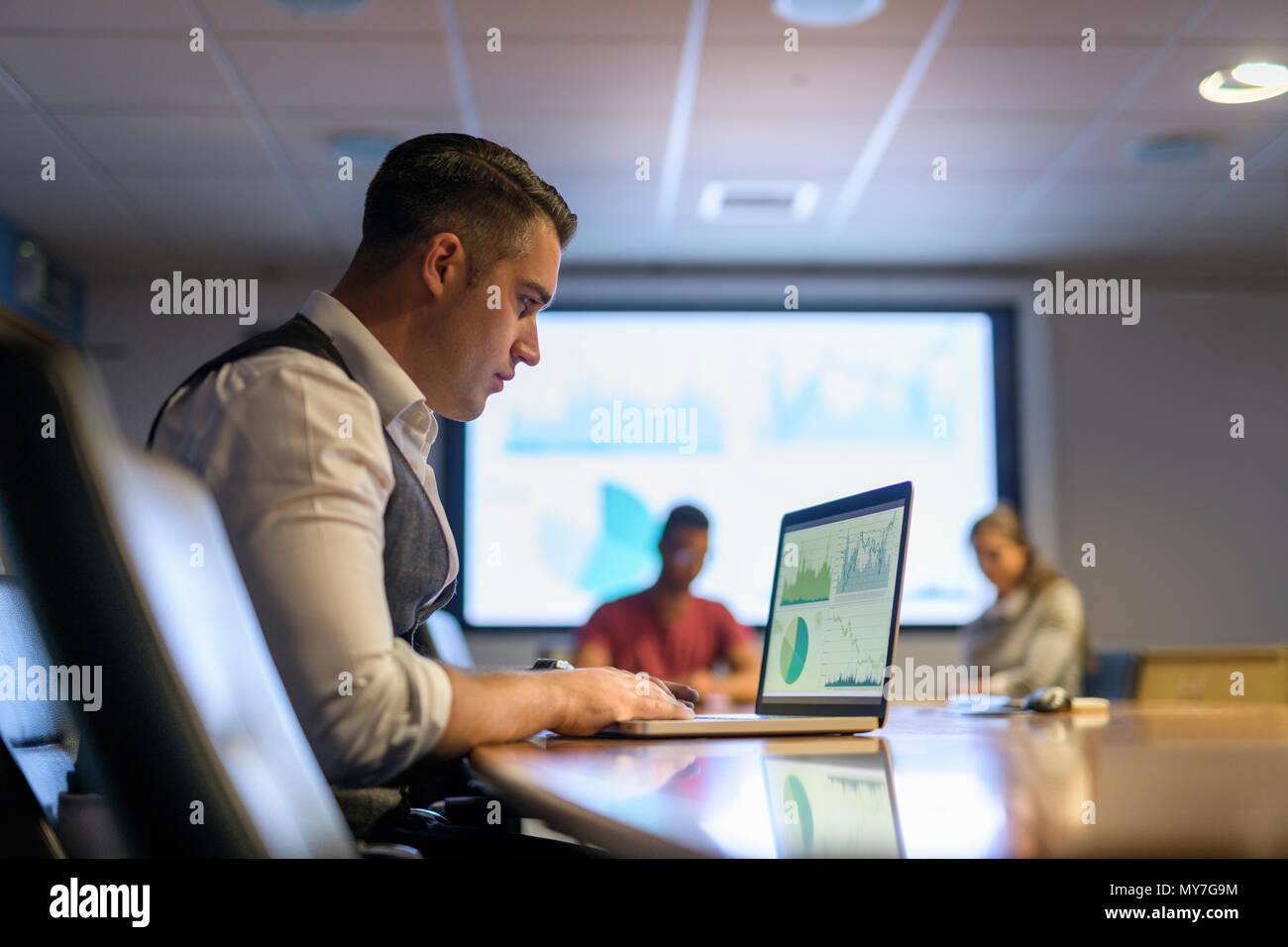 Uomo d affari con computer portatile nella riunione di affari Immagini Stock