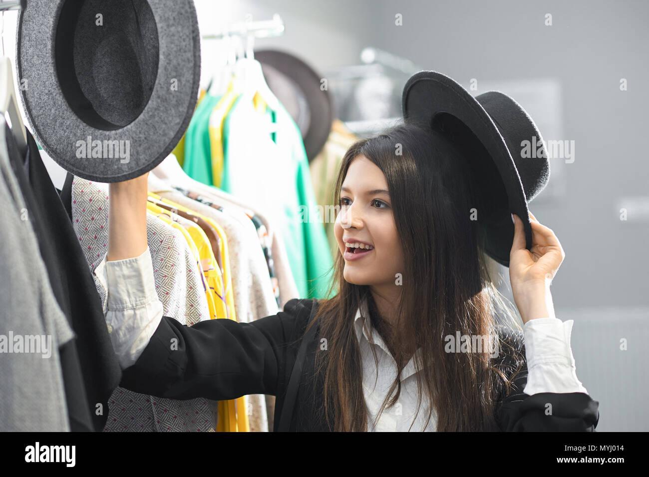 6237a4106254 Ragazza sorridente cercando su eleganti e moderni black hats in negozio di  abbigliamento. In piedi