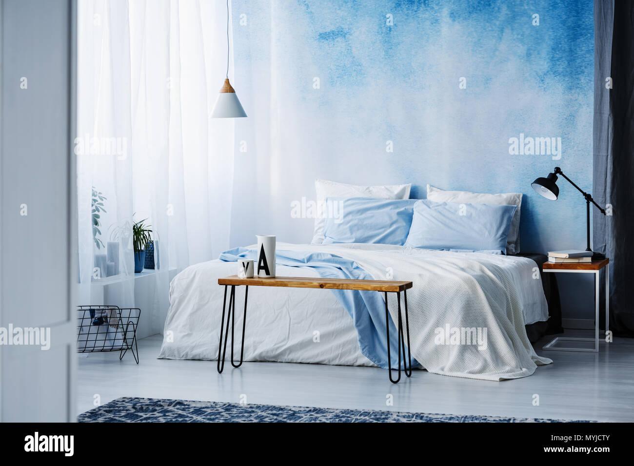 La lampada sul tavolo di legno accanto ad un blu e bianco letto