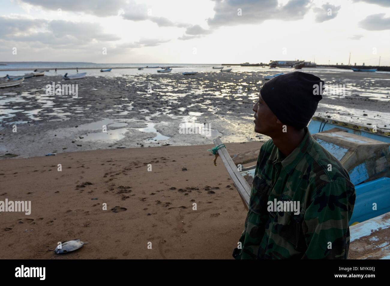 Gibuti , Obock, da qui i migranti etiope tentano di attraversare i Bab el Mandeb, Mar Rosso, il Golfo di Aden dal contrabbandiere barche nello Yemen per continuare il viaggio in Arabia Saudita o in Europa, migrante etiope guardando al mare / DSCHIBUTI, Obock, Meerenge Bab el Mandeb, Mit Hilfe von Schleppern versuchen aethiopische Migranten hier nach Jemen ueberzusetzen, um weiter nach Saudi Arabien oder Europa zu gelangen Immagini Stock
