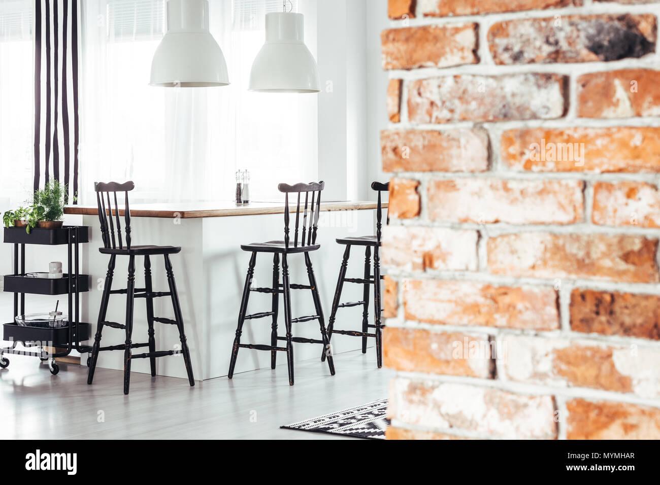 Rosso mattone parete nella sala da pranzo rustica con luci bianche