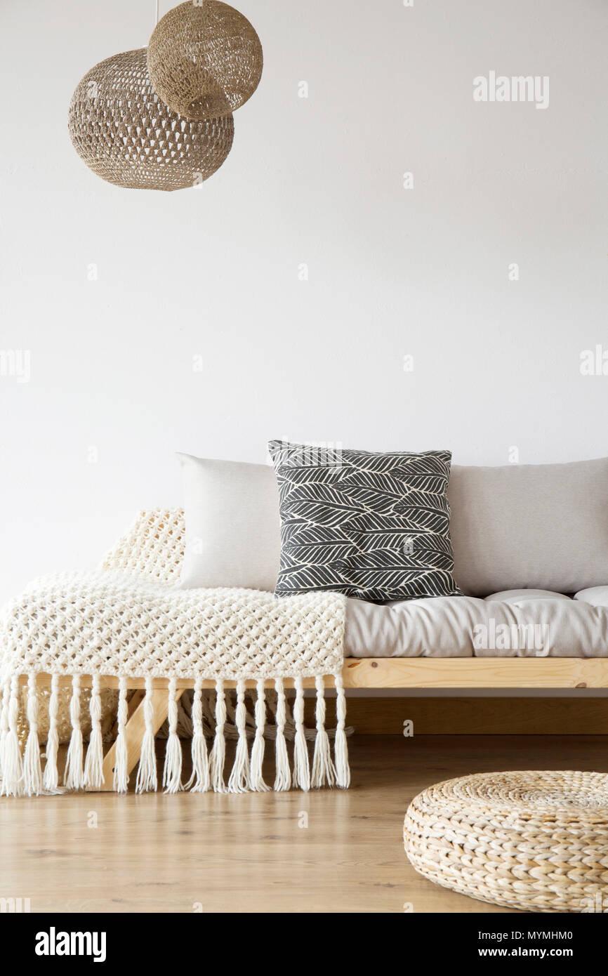Coperta modellato sul letto in legno, pouf e lampade in una ...