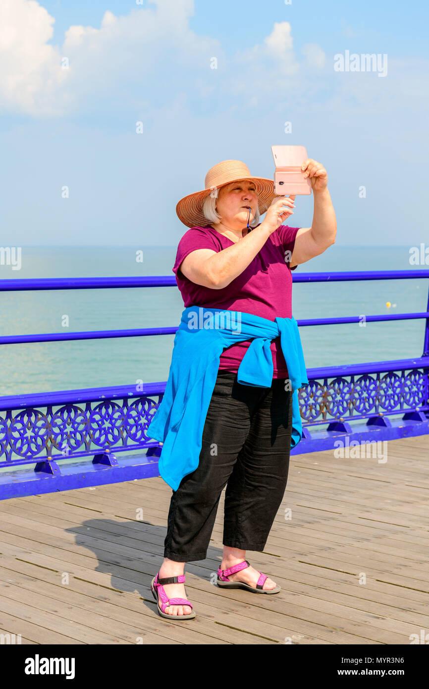Donna di mezza età tenendo un selfie su Eastbourne Pier Immagini Stock