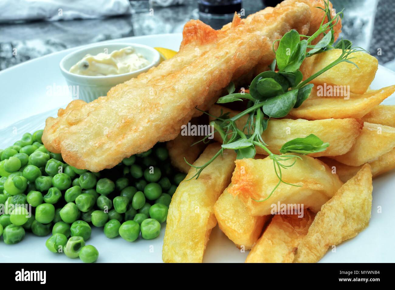 Croccante pesce martoriato e chunky patatine fritte servite con bolliti di piselli verdi e maionese, cibo inglese tradizionale . Immagini Stock