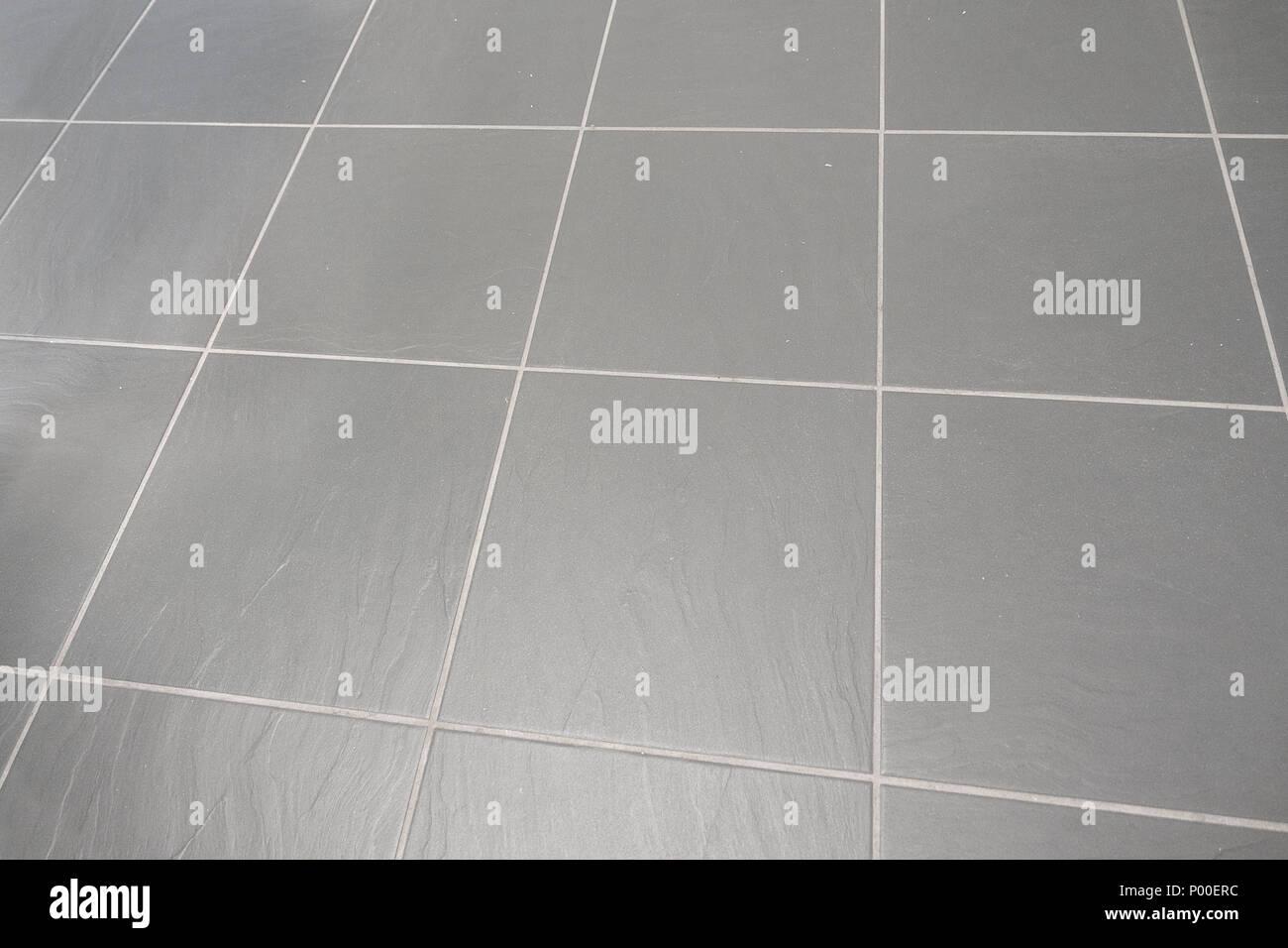 Piano con grande grigio piastrelle quadrate e boiacca foto