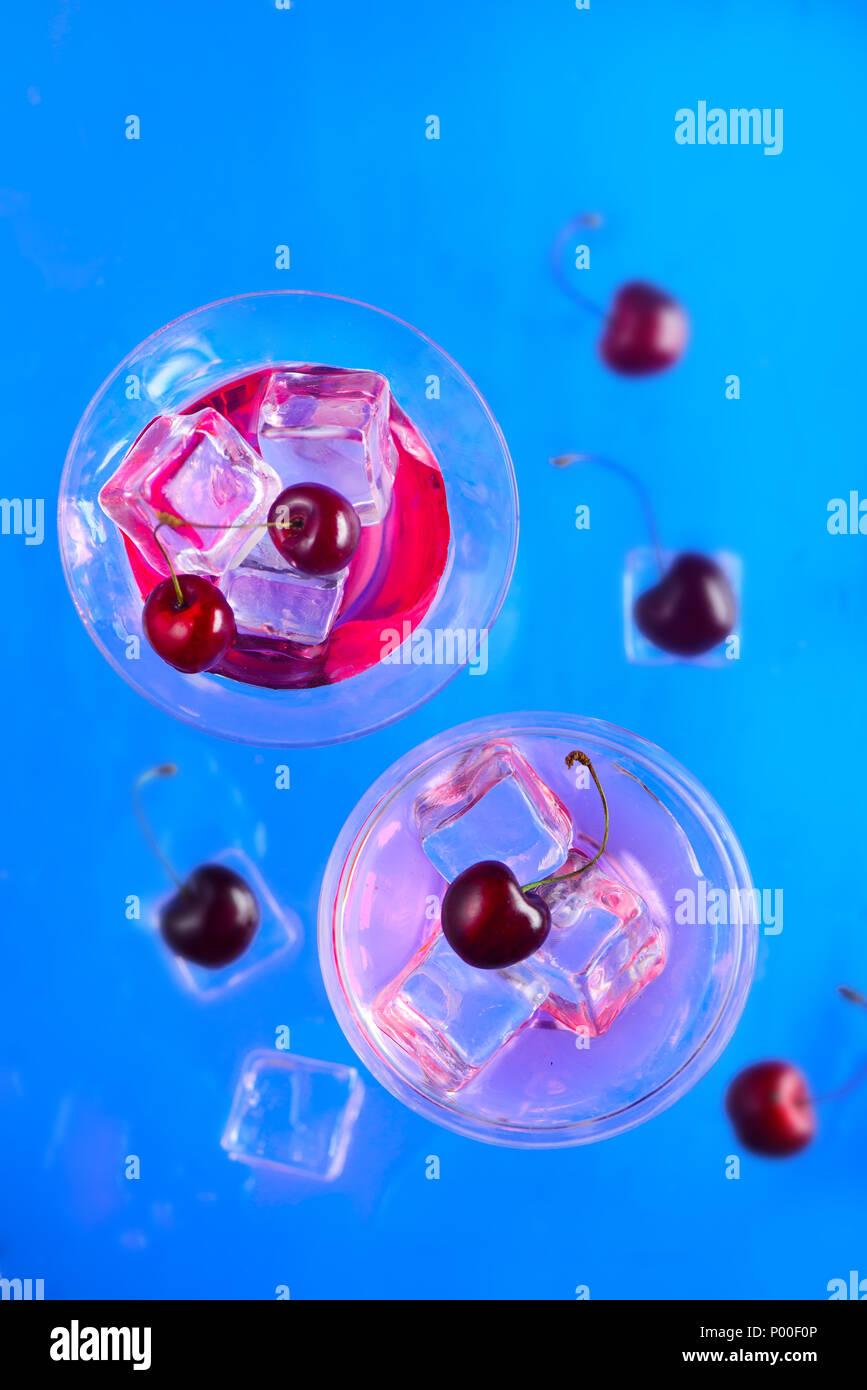 La ciliegia sidro bicchieri da cocktail dal di sopra su uno sfondo blu. Rinfrescanti drink freddo laici piatta con spazio di copia Immagini Stock