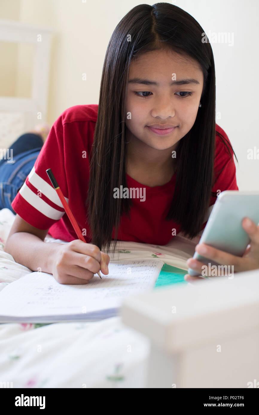 Ragazza distesa sul letto utilizzando il telefono cellulare per aiutare con i compiti Immagini Stock