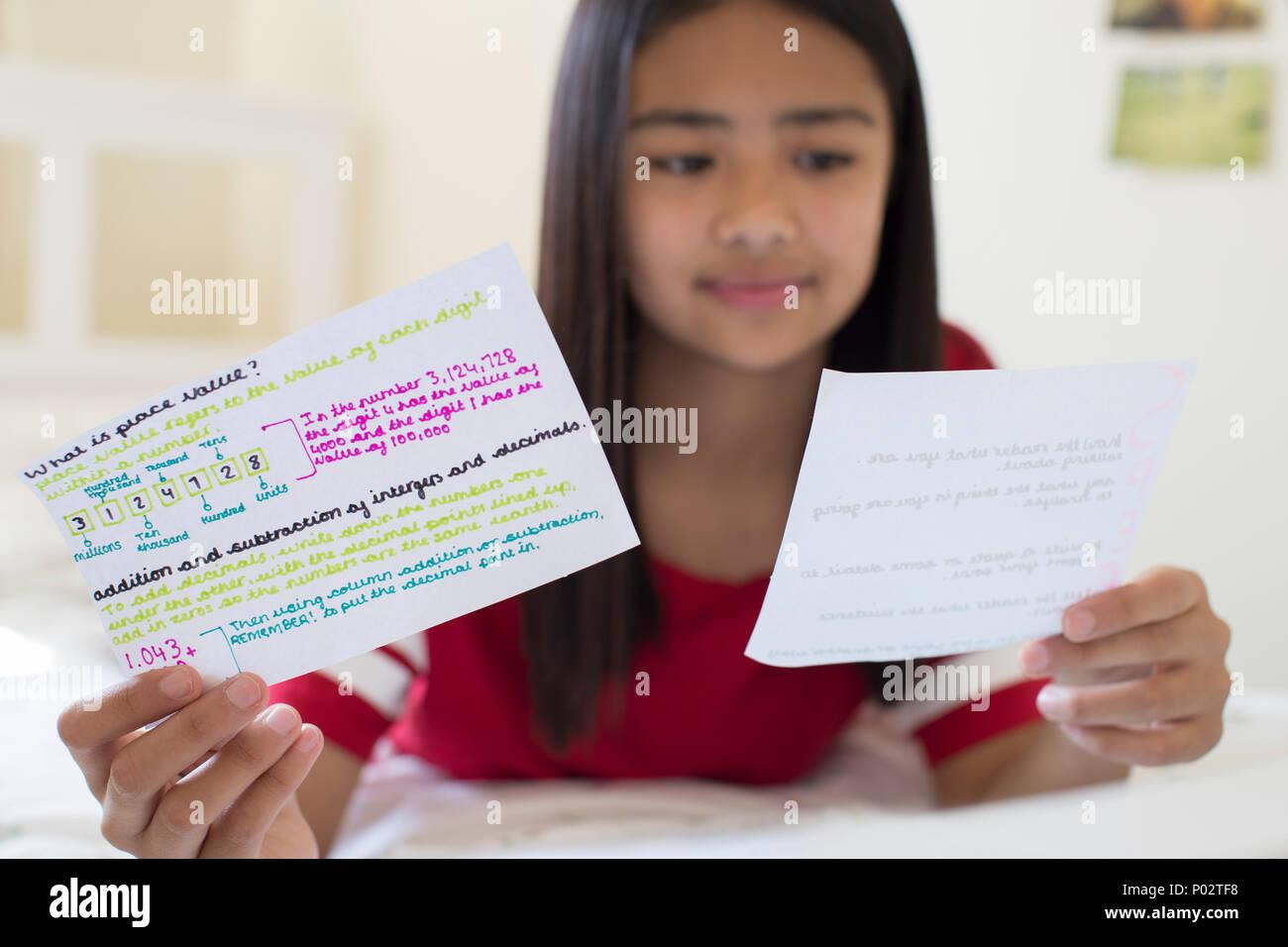 Ragazza distesa sul letto scritto utilizzando le schede di studio per aiutare con la revisione Immagini Stock