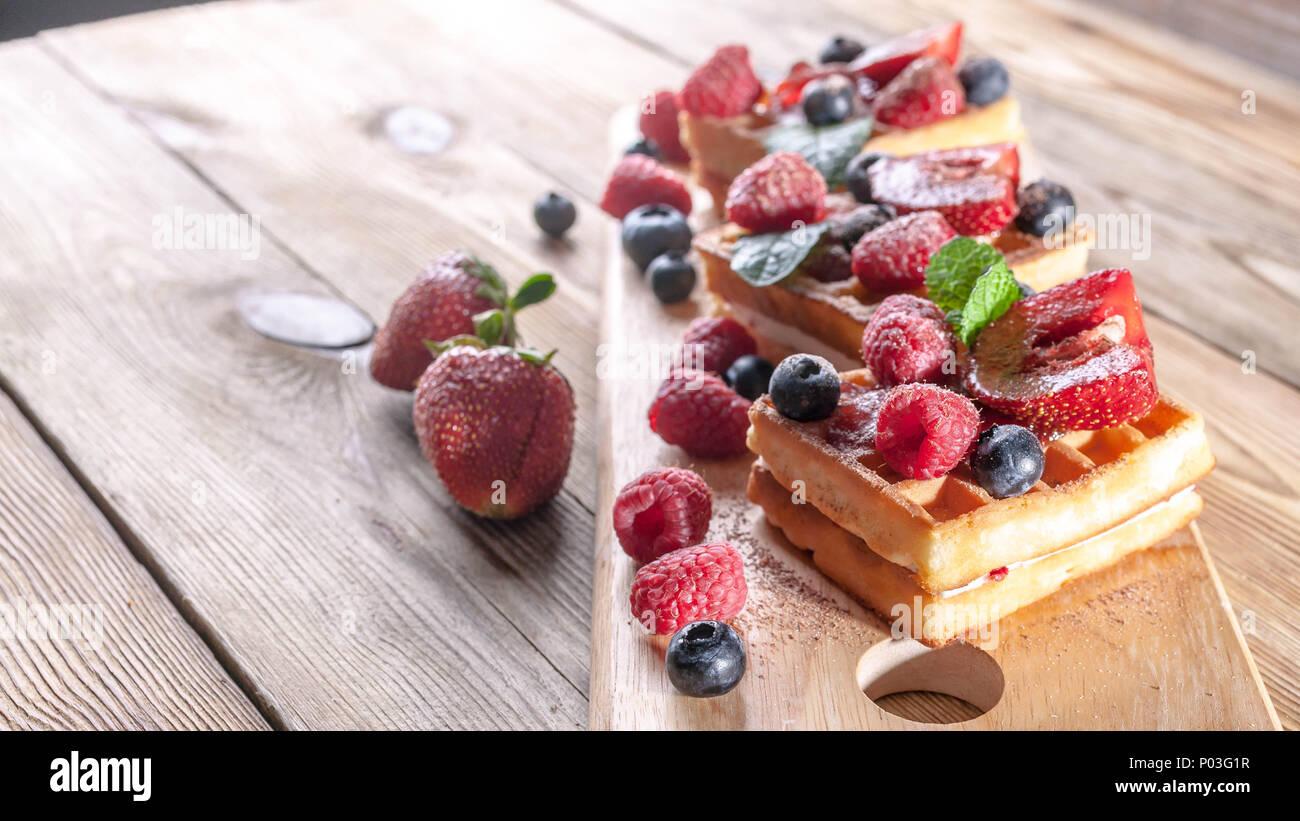 Cialde viennese con confettura di fragole, fresche fragole, lamponi mirtilli e scaglie di cioccolato su un tavolo di legno. La deliziosa prima colazione concept Immagini Stock