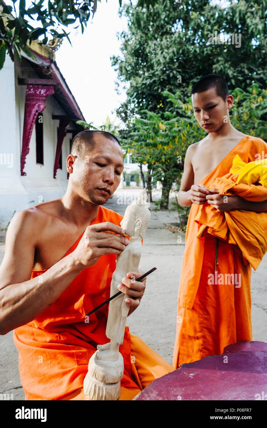 Luang Prabang, Laos, sud-est asiatico : un monaco buddista si ritaglia un di legno BUDDA STATUETTA come un giovane debuttante guarda, in un monastero a Luang Prabang. Immagini Stock