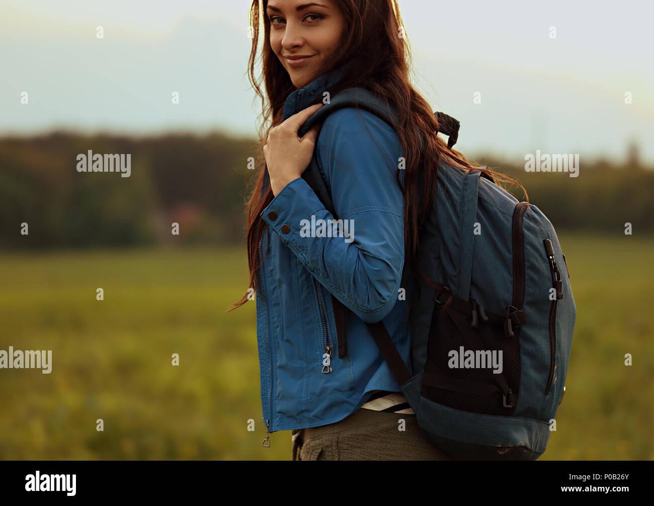 Felice backpacking avventurosa donna hanno un viaggio di campeggio con blue enorme musetta sulla natura Sera d'estate sfondo Immagini Stock