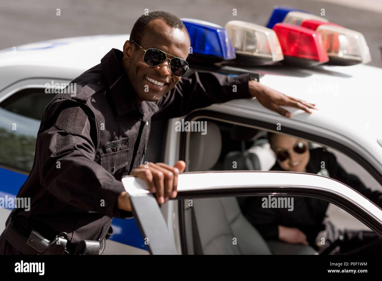 Felice giovani funzionari di polizia con auto guardando la fotocamera Immagini Stock