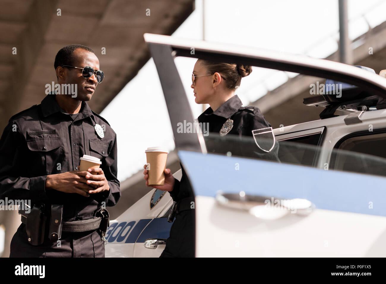 Rilassante giovani funzionari di polizia di bere il caffè vicino auto della polizia. Immagini Stock