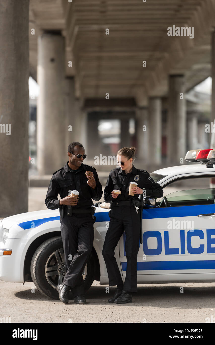 I funzionari di polizia con caffè e ciambelle in piedi accanto a AUTO Foto Stock