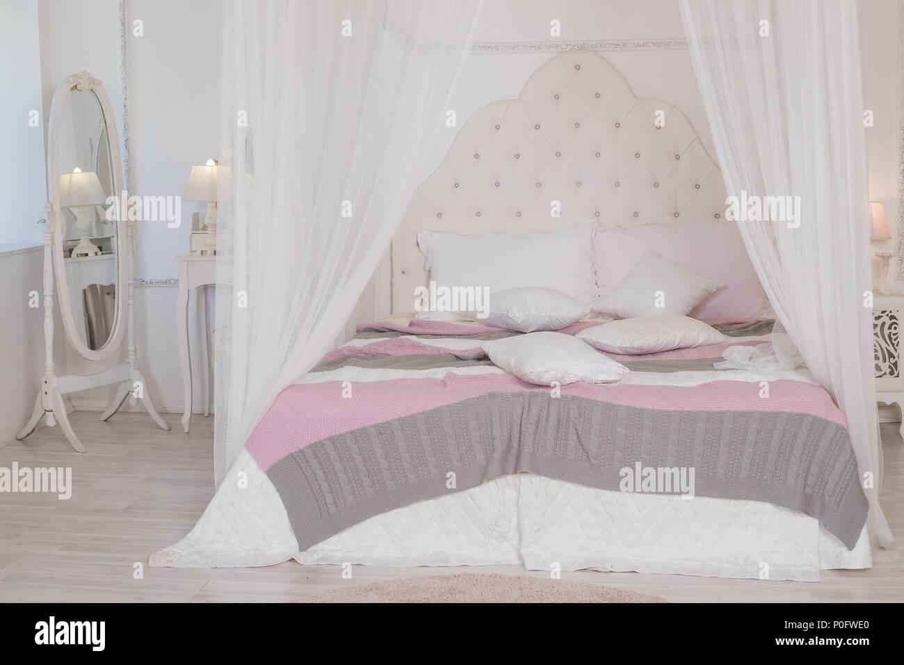 Letto grande con graziosi letti pastello nella donna di camera. Camera da letto moderno in colori pastello. letto a baldacchino.semplicità scandinava di design. Eco appartamenti loft. Immagini Stock
