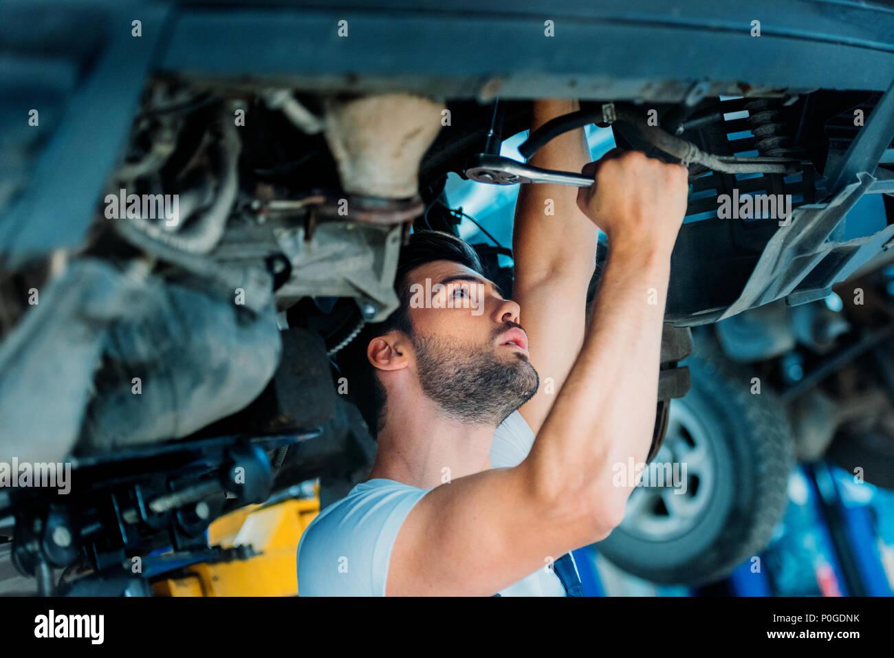 Automechanic lavorando su un sollevato auto in una officina di riparazione. Immagini Stock
