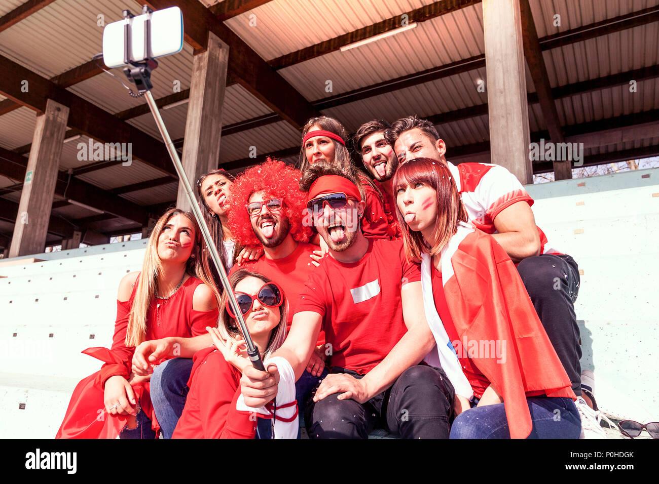 Gruppo di fan vestiti di rosso il colore prende un selfie nelle gabbie di  uno stadio e2beb1998fa