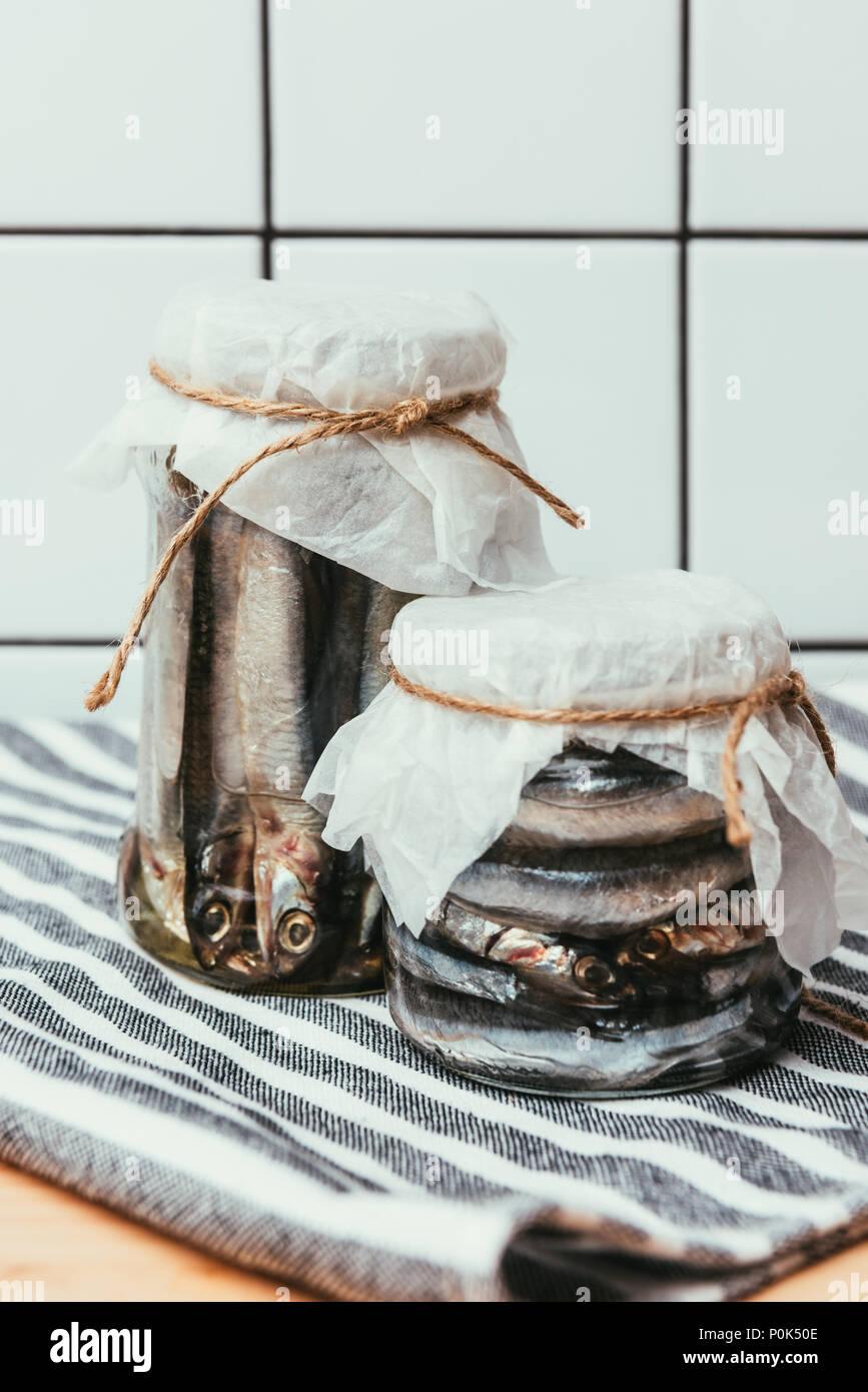 Pila di pesce salato in vasetti avvolti da stringhe su asciugamano Immagini Stock