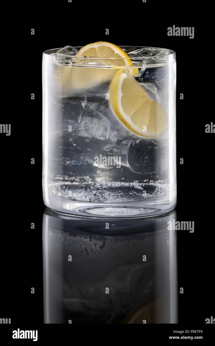 Il gin tonic in rocce isolate di vetro su nero Immagini Stock