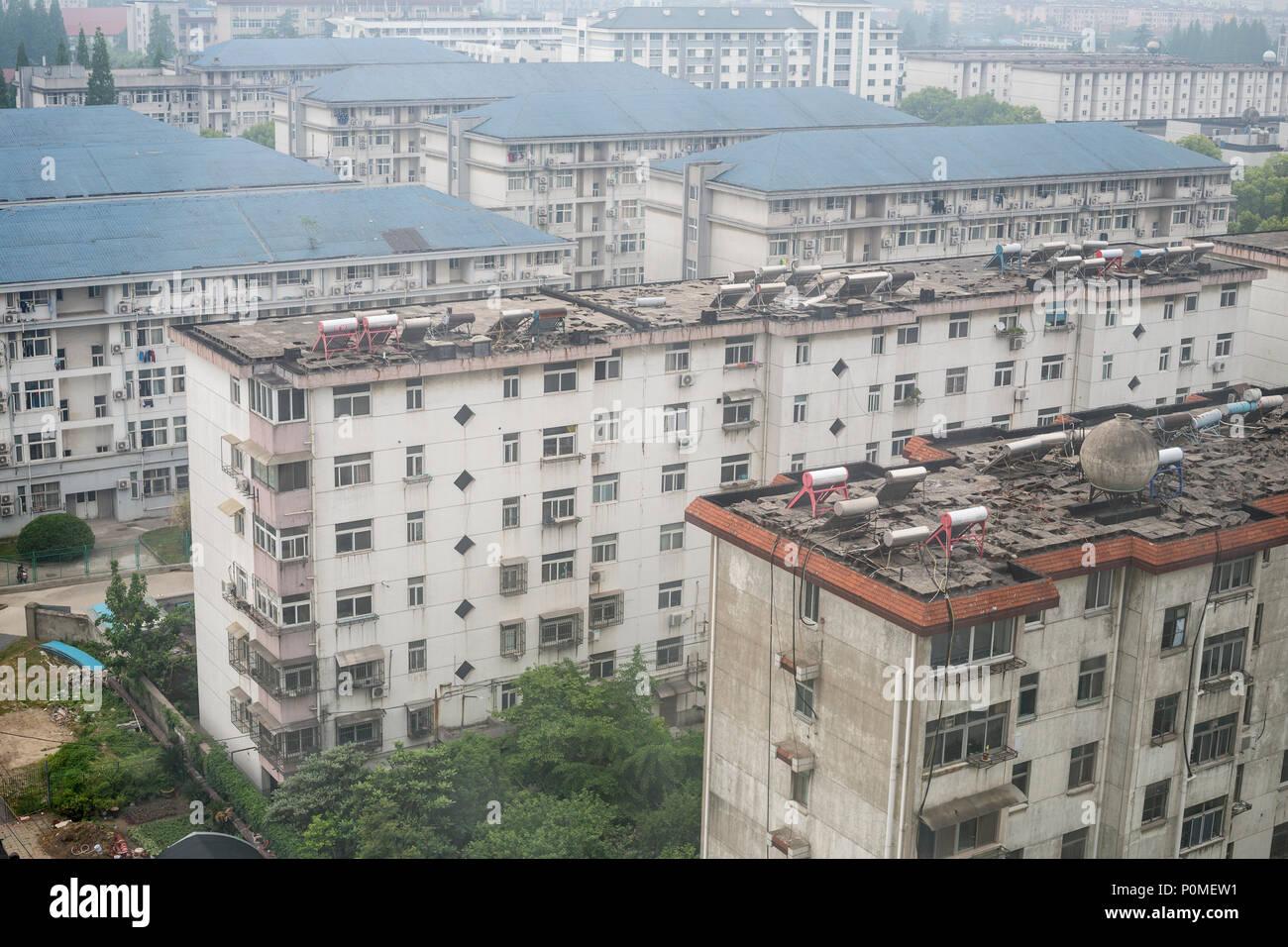 Yangzhou, Jiangsu, Cina. Caloriferi di Acqua Solari su tetti di edifici di appartamenti. Inquinamento dell'aria. Immagini Stock