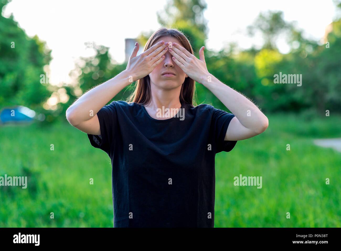 La bruna ragazza in estate in un parco della natura. Gesti delle mani  chiuse gli b552df2bfcf