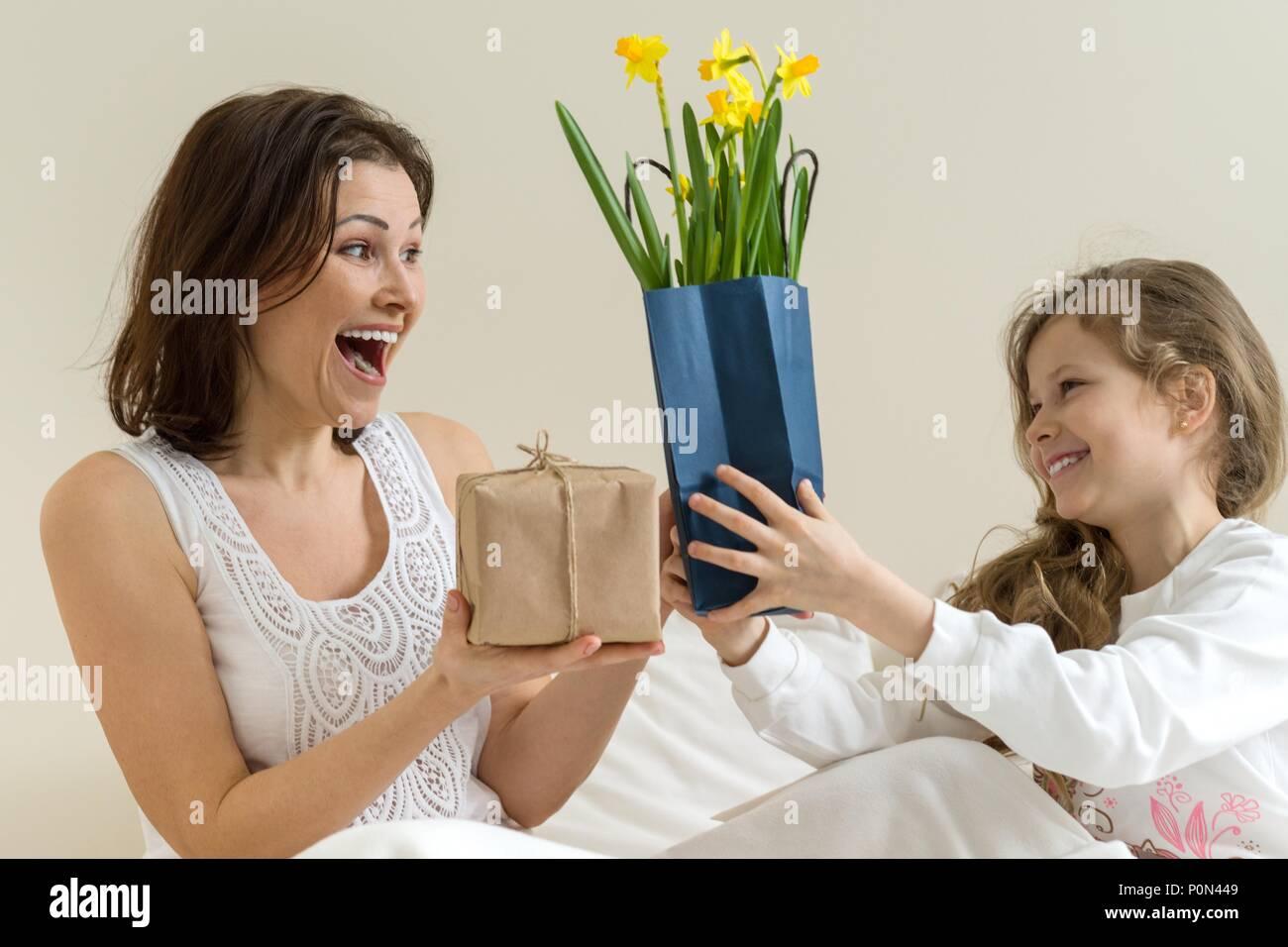 La festa della mamma. La piccola figlia mantiene un regalo e fiori ...