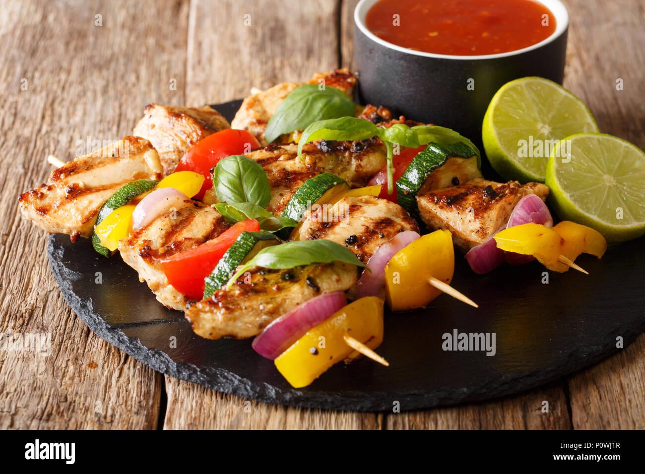 Servito pollo grigliato kebab spiedini con verdure con salsa di erbe e di calce closeup su una piastra di ardesia su una tavola orizzontale. Immagini Stock