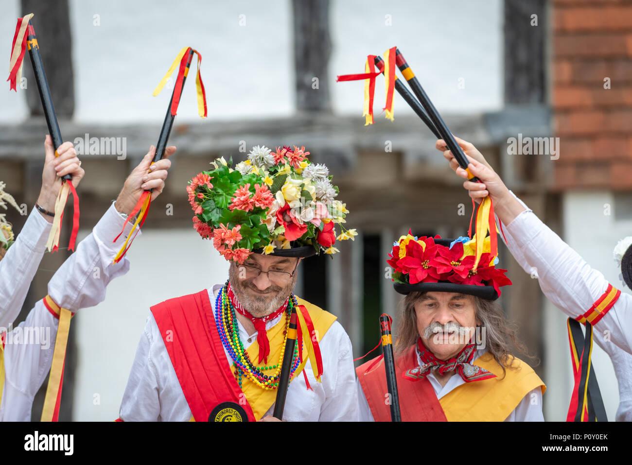 Morris ballerini indossando cappelli estivi coperto di fiori e indossando  costumi tradizionali ballare durante una morris a39f7f7661ab