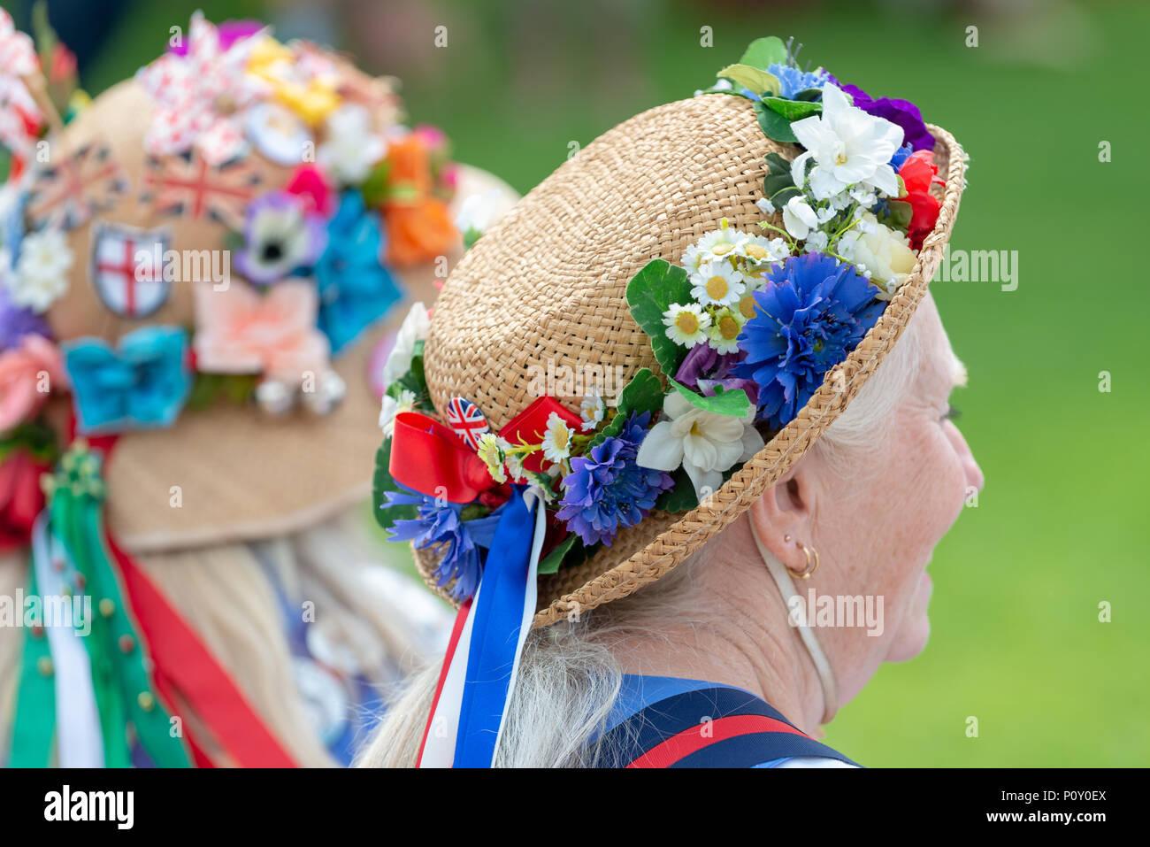 Female morris ballerini indossando cappelli estivi ricoperto di fiori  colorati e nastro di chattare mentre 15c89adc6f28