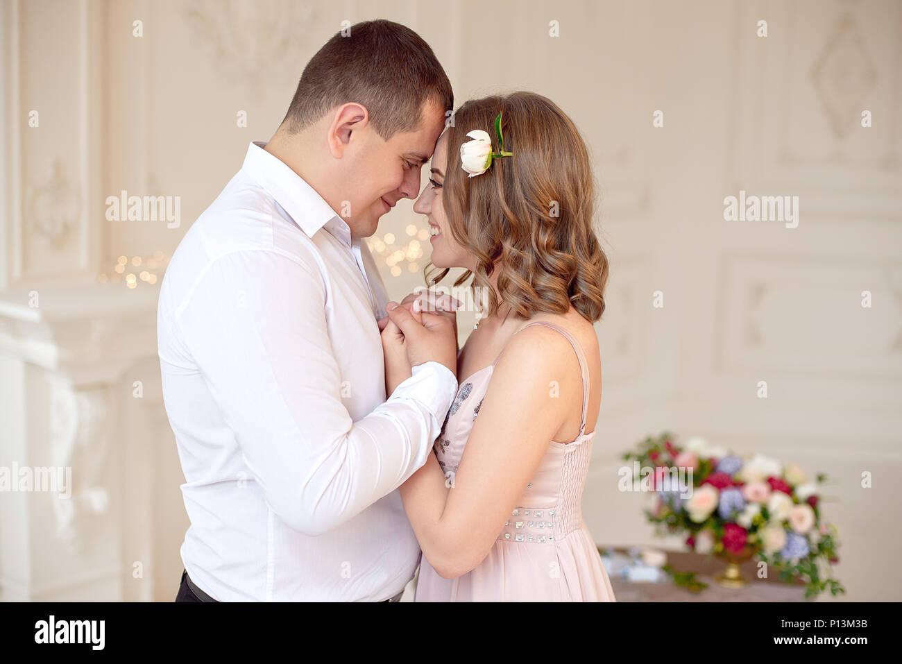 Close-up giovane coppia felice baciare in camera bianca. Immagini Stock