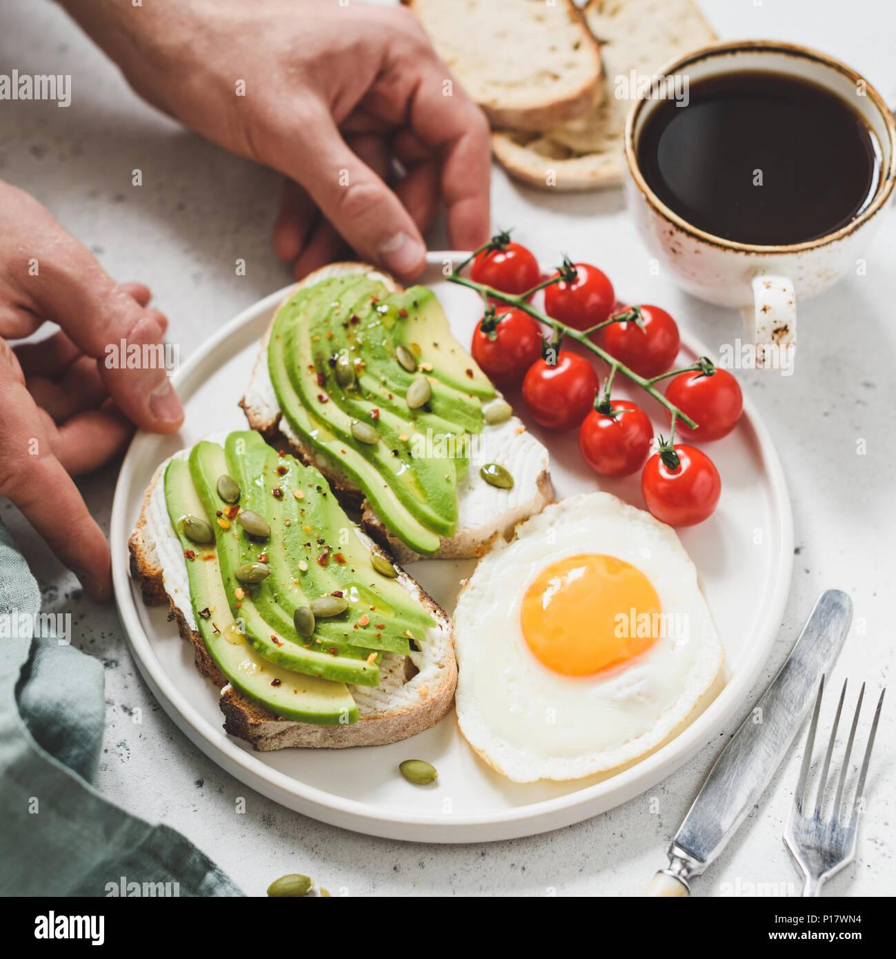 Toast con avocado, Uovo fritto, pomodori e tazza di caffè. Una sana prima colazione. Mani tenendo la piastra con una sana prima colazione il cibo. Concetto di vita sana Immagini Stock