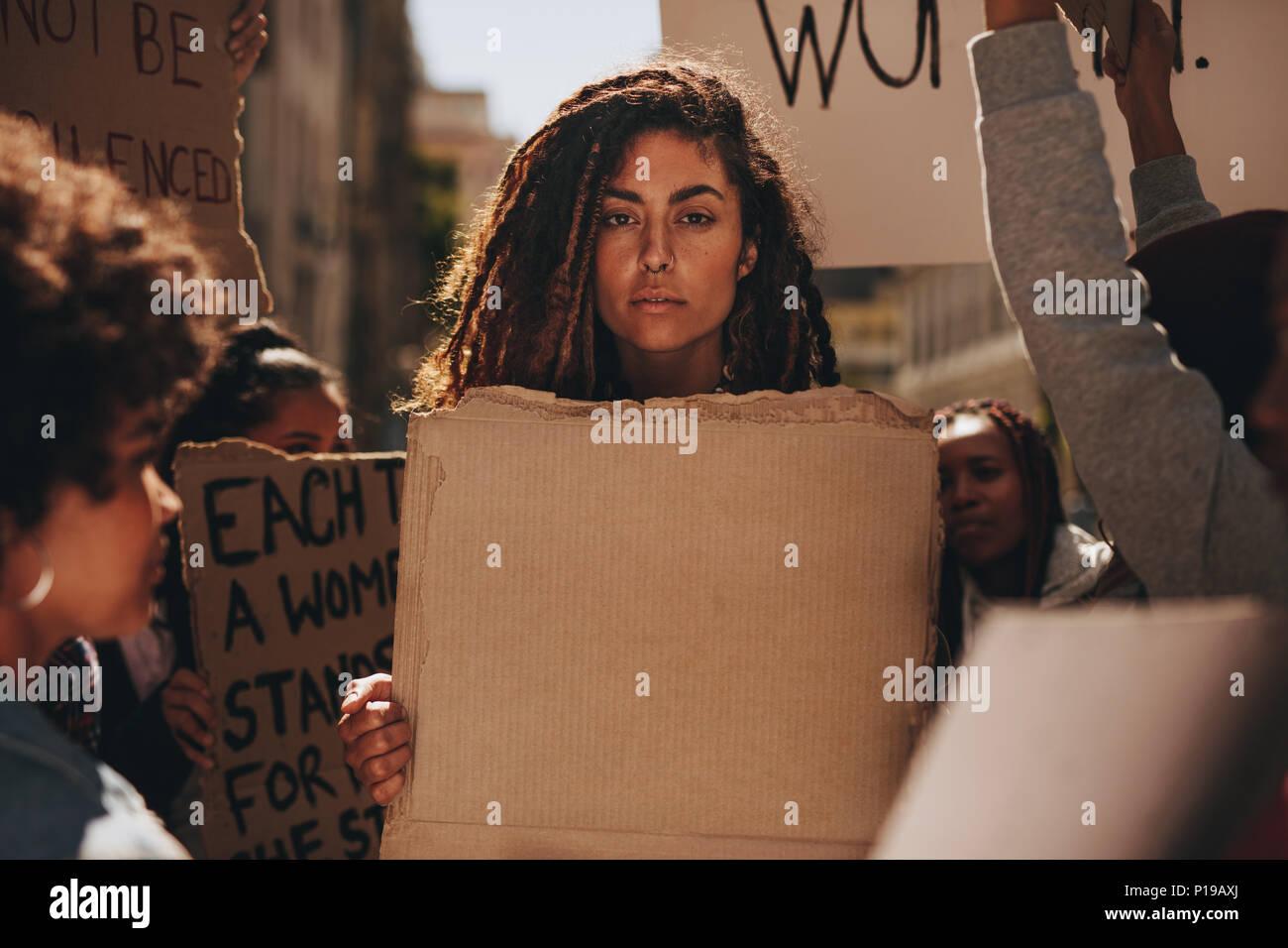 Grave donna tenendo una targhetta vuota durante una manifestazione di protesta all'esterno. Un gruppo di dimostranti femmina su strada con striscioni. Immagini Stock