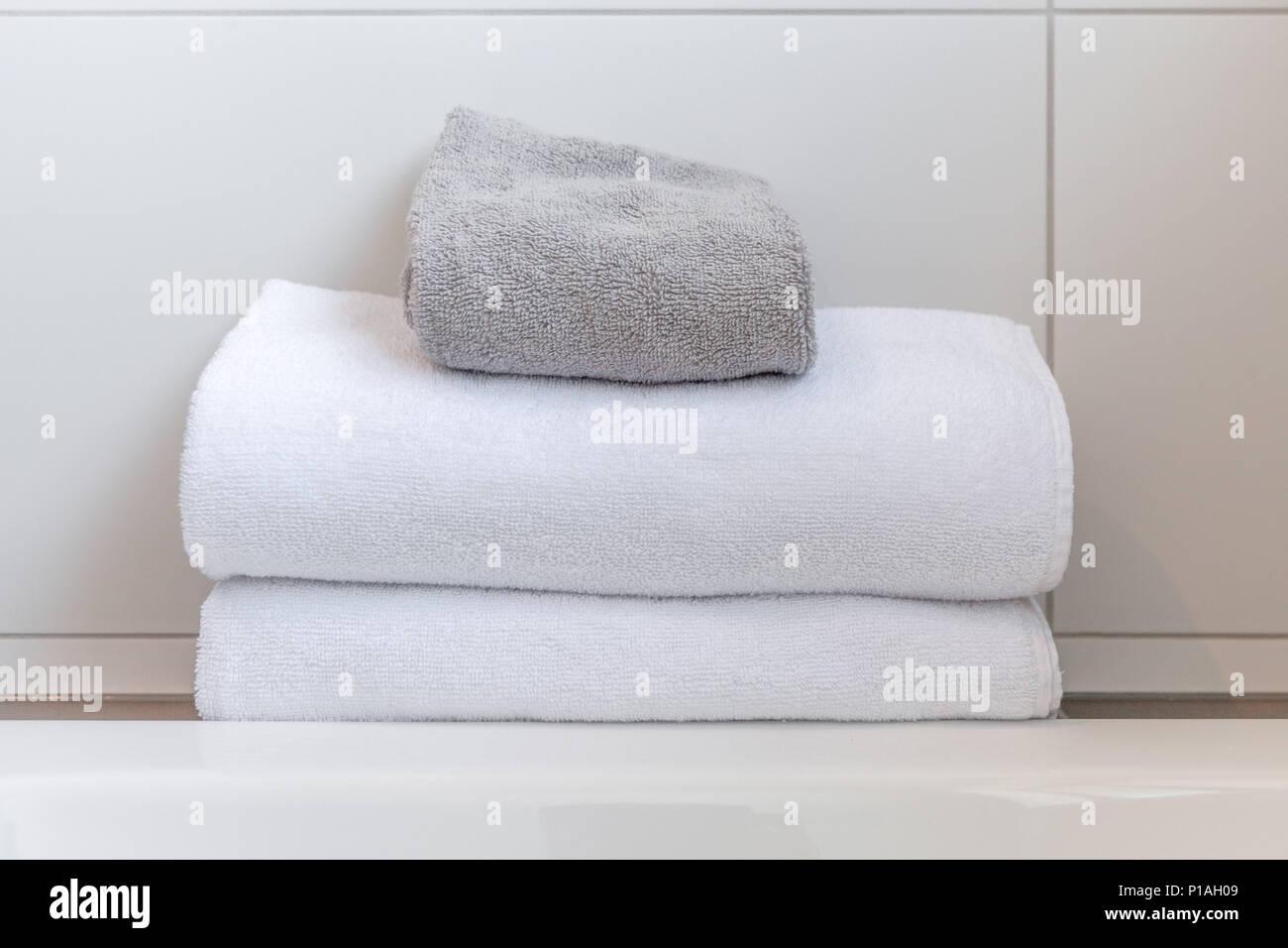 Bianco e grigio asciugamani ripiegati contro le piastrelle bianche