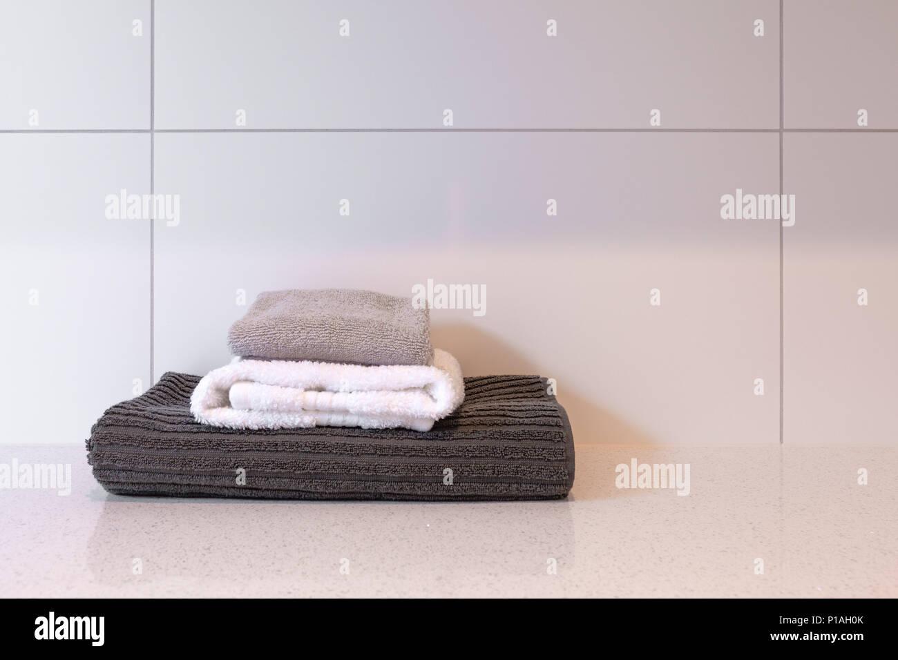Ripiegato gli asciugatutto da cucina contro le piastrelle bianche